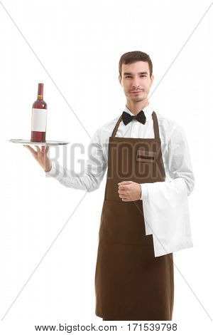 Cute waiter holding silver tray with bottle of wine over white background