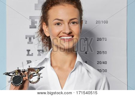 Young woman with trial frame near eyesight test chart background