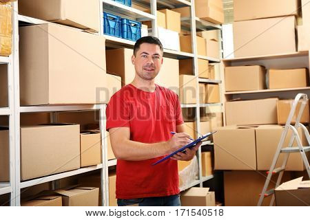 Young businessman with clipboard at warehouse