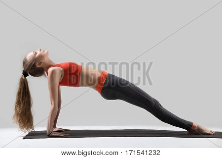 Young attractive yogi woman practicing yoga, doing Purvottanasana exercise, Upward Plank pose, working out, wearing sportswear, red sports bra, pants, full length, isolated, grey studio background
