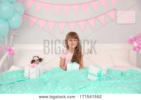 Cute birthday girl in bed with giftboxes
