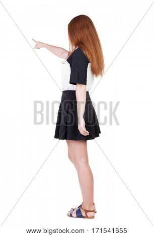 Back view of young redhead woman pointing at wall. beautiful girl in dress. Rear view people collection. backside view of person. Isolated over white background.