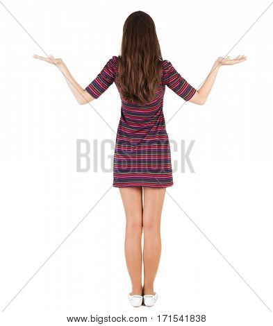 Back view of Beautiful woman in  dress looking at wall and Holds a hand up. Rear view people collection.  backside view of person.  Isolated over white background. skinny girl is holding something
