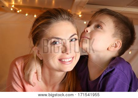 Young woman and cute boy in hovel at home