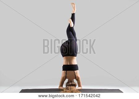 Young yogi woman practicing yoga, standing in headstand exercise, Garuda salamba sirsasana pose, working out, wearing sportswear, black sports bra, pants, full length, isolated, grey studio, rear view