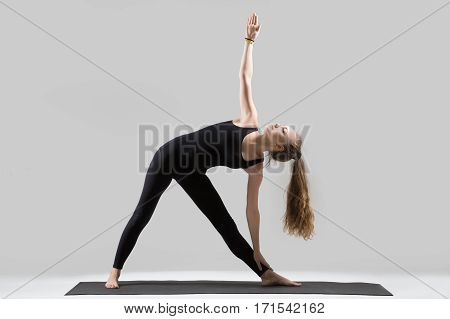 Young attractive yogi woman practicing yoga, standing in Utthita Trikonasana exercise, extended triangle pose, working out, wearing sportswear, black tank top, pants, indoor full length, grey studio