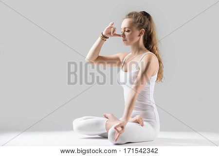 Young woman yogi practicing yoga, sitting in Padmasana, Lotus pose, using Alternate Nostril Breathing, nadi shodhana pranayama, working out, wearing white tank top, pants, full length, grey studio