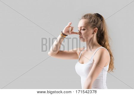 Portrait of young attractive yogi woman practicing yoga, using Alternate Nostril Breathing, nadi shodhana pranayama, working out wearing white tank top, grey studio background, closeup, eyes closed