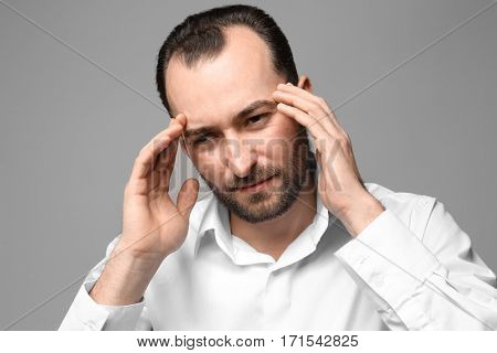 Handsome man suffering from headache, on color background