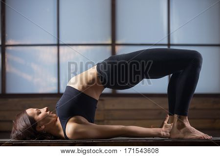 Young attractive woman practicing yoga, stretching in Glute Bridge exercise, dvi pada pithasana pose, working out, wearing sportswear, black tank top, pants, indoor full length, evening practice