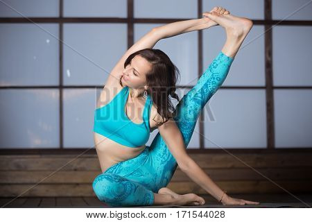 Young smiling attractive woman practicing yoga, stretching in Surya Yantrasana exercise, Compass pose, working out, wearing sportswear, blue tank top, pants, indoor full length, evening practice