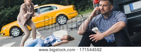 Car driver calling an ambulance stressed woman trying to help an unconscious bike driver after accident