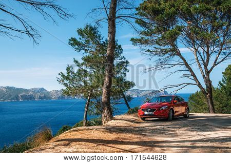 Alcudia Mallorca Spain - May 23 2016: Seascape of Mediterranean Sea with a red car Volvo V40 traveling on the mountain serpentine through the pine forest along the coast of Majorca