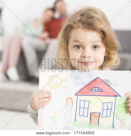 Boy Holding Drawing With Parents
