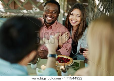 Happy intercultural couple looking at camera by festive table
