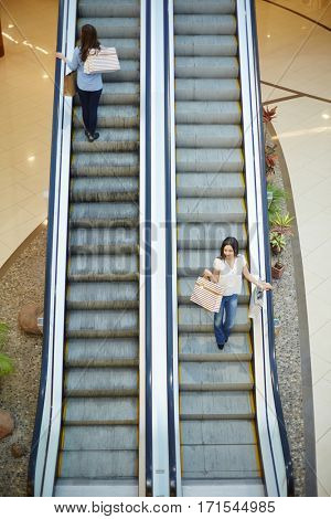 Young shoppers moving up and down on escalator