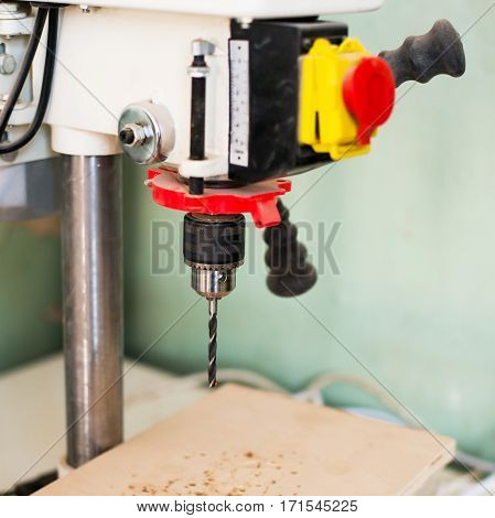 close-up of a professional drill press in a cerpenter's workshop