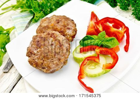 Cutlets stuffed with spinach and egg, salad with tomatoes, cucumber and pepper in a dish, basil and parsley on a wooden board background
