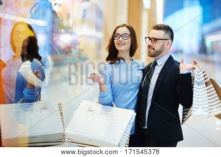 Young modern couple standing by shop-window