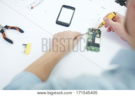 Closeup top view shot of male hands attaching parts to opened circuit board of disassembled smartphone in workshop
