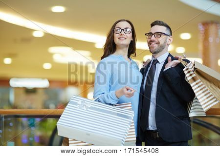 Couple of shoppers with paperbags looking at shop-display