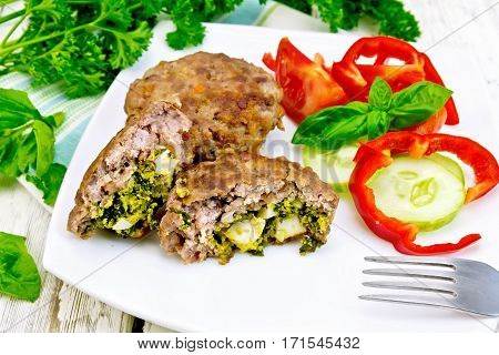 Cutlets stuffed with spinach and egg, salad with tomatoes, cucumber and pepper in a dish on a towel, basil and parsley on a wooden board background