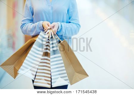 Several paperbags in hands of shopaholic