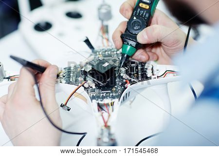 Closeup top view shot of male hands testing electric current in circuit board of disassembled drone using multimeter tool on table in maintenance shop