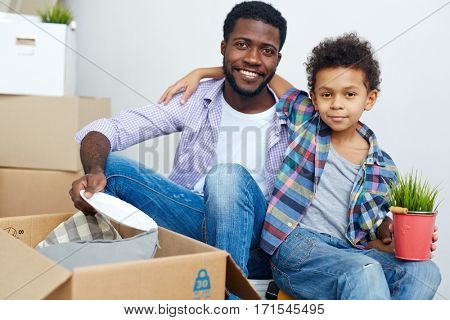 Little son and his father unpacking things from carton box
