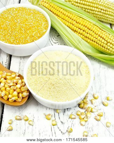 Two bowls with grits and flour corn, a spoon with grains, cobs on the background of wooden boards