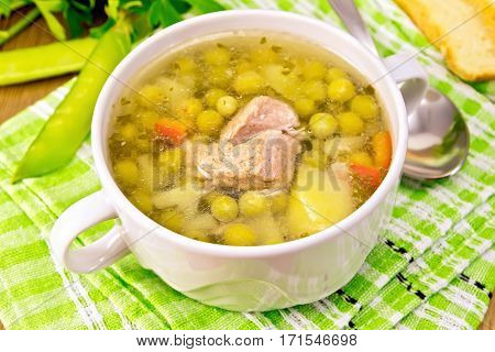 Soup of green peas with meat and potatoes in a white bowl, bread, spoon, pods on green napkin at the background of the wooden planks