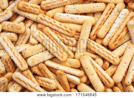 Bread sticks with poppy seeds as background