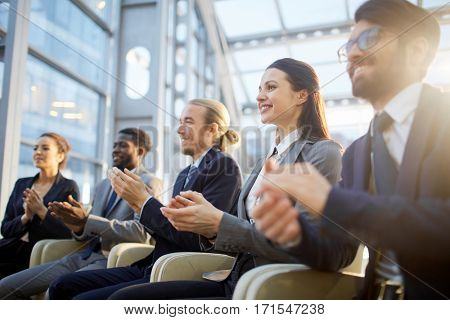 Successful business staff applauding to speaker