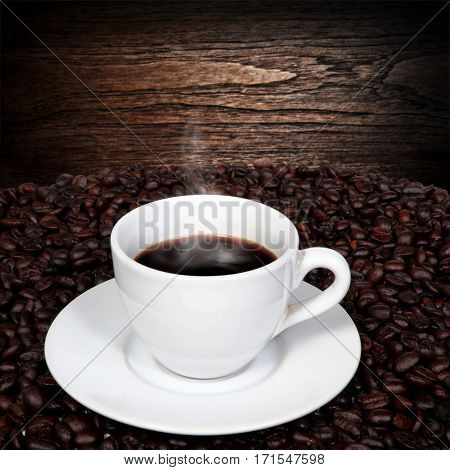 Black coffee in cup and coffee beans with smoke on old wood background.