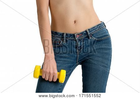 asian woman with toned stomach holding yellow dumbbell in blue jeans isolated on white background.