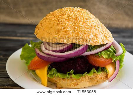 Hamburger with beetroot Cutlets on a wooden table and ingredients