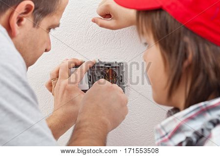 Young boy watches as his father installs an electrical wall socket on white plastered wall - focus on hands