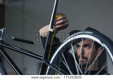 Serious bearded craftsman taking measurements of bicycle