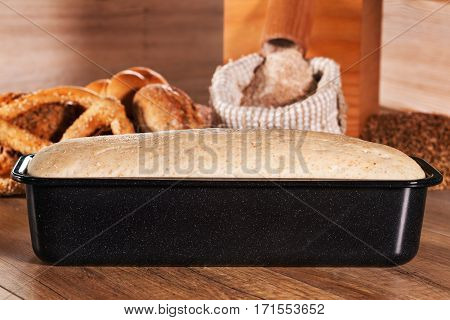 Bread dough leaven in baking mold in front of wheat mill and bakery products