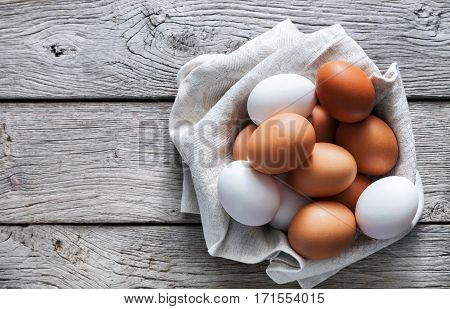 Fresh chicken brown and white eggs on linen napkin at rustic wood table. Top view with copy space. Rural still life, natural healthy food and organic farming concept.