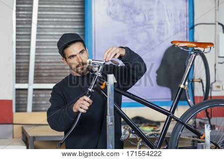 Young bearded man in black cap working with bicycle