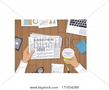 Business news. Businessman holding a newspaper and coffee to go on the wooden desktop. Coffee break, breakfast, lunch, documents, laptop, phone, purse, notebook. View from above
