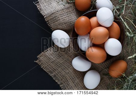 Poultry farm concept. Bowl with fresh brown and white eggs on burlap textile isolated on black background with copy space. Top view on sacking and hay. Rural still life, natural organic healthy food.