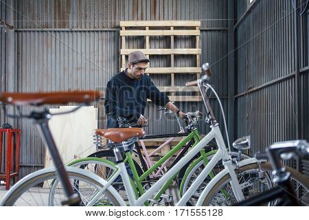 Man in cap assembling several crafted bicycles on his workshop