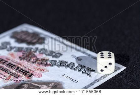 Dice, cube in a winner space. Six of six. Old Swedish banknote on a black background.