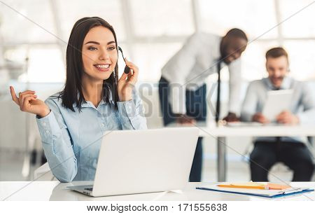 Attractive business woman in headset is smiling while working with laptop in office her colleagues in the background
