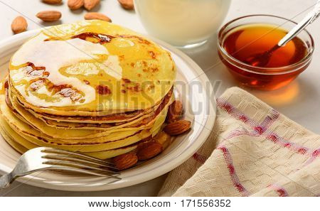 Pancakes with honey and almond on a white background