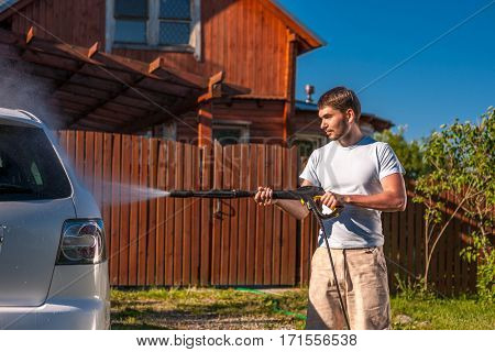 Man washing car with jet spray gun on open air in front of house