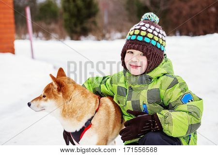Little Kid With Shiba Inu Dog Outdoors In The Winter