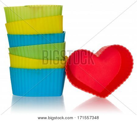 Hearts molds for cookies in red yellow green blue. Silicone moulds arranged in a pile on a white background with slight reflection.